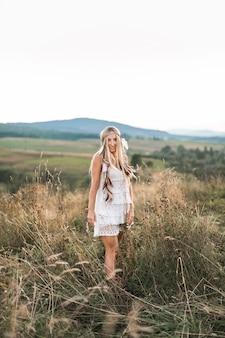 Jong blond mooi hippiemeisje in witte kleding op de zomergebied