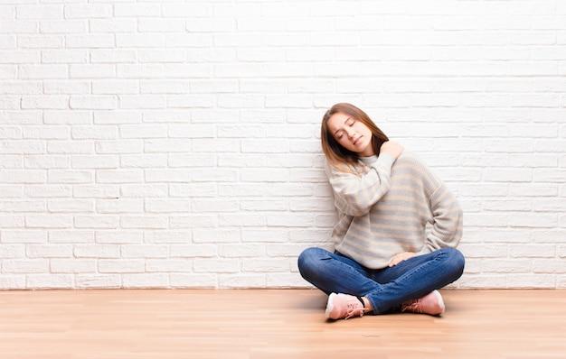 Jong blond mooi meisje dat zich moe, gestrest, angstig, gefrustreerd en depressief voelt, lijdt aan rug- of nekpijn zittend op de vloer
