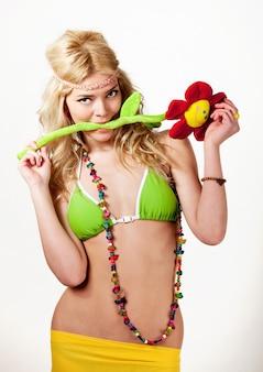 Jong blond mooi vrouwenmodel in groene bikini en gele pareo met kleurrijke toebehoren die en camera over witte achtergrond in fotostudio bevinden bekijken. schoonheid en mode levensstijl concept