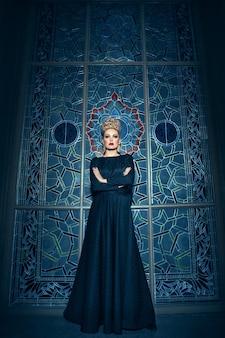 Jong blond vrouwelijk model, gekleed in een lange zwarte jurk, met een grote kroon van elegant kapsel