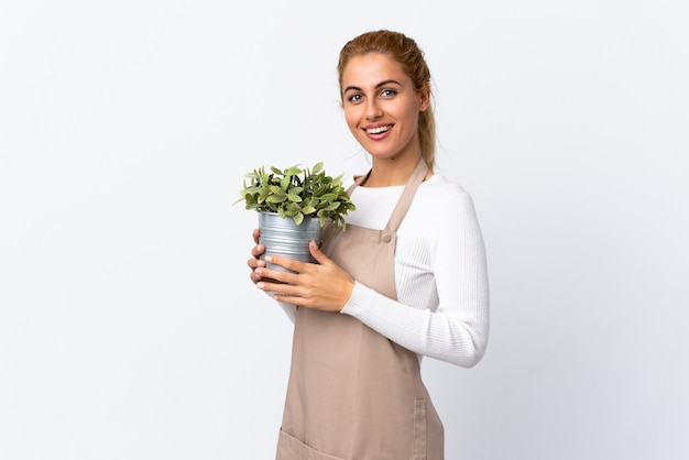 Jong blonde de vrouwmeisje die van de tuinman een installatie over het witte muur toejuichen houden