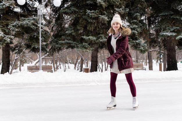 Jong blonde kaukasisch meisje dat pret in de winterpark heeft. wintervakantie concept