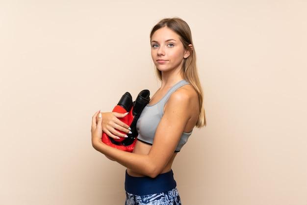 Jong blonde sportmeisje over geïsoleerde muur met bokshandschoenen