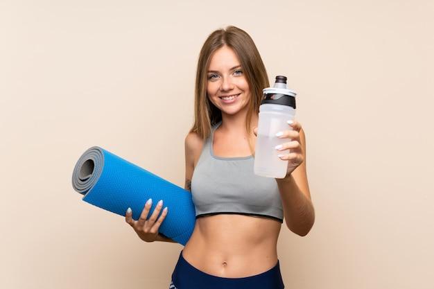 Jong blonde sportmeisje over geïsoleerde muur met de fles van het sportenwater en met een mat
