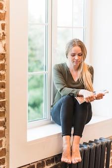 Jong blonde vrouw met tijdschrift in haar hand zittend op de vensterbank