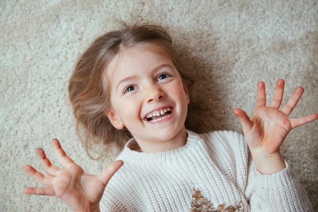 Jong blondemeisje dat thuis glimlacht