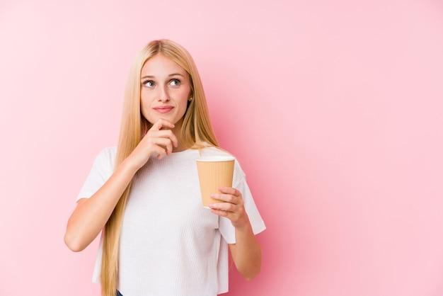 Jong blondemeisje die een afhaalkoffie houden die zijwaarts met twijfelachtige en sceptische uitdrukking kijkt.