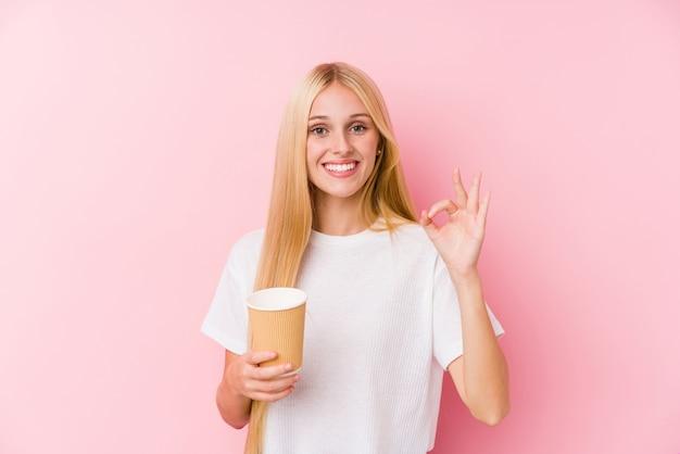 Jong blondemeisje die een meeneemkoffie vrolijk en zeker houden tonend ok gebaar.