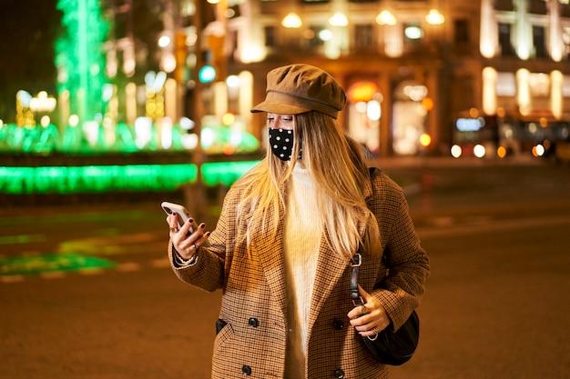 Jong blondemeisje die met masker iets op haar telefoon bekijken. ze is 's nachts in een stad. winterse sfeer.