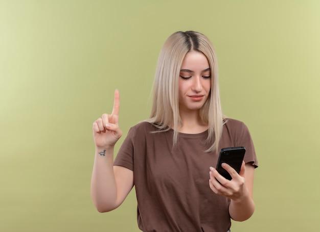 Jong blondemeisje die mobiele telefoon houden die het met opgeheven vinger op geïsoleerde groene muur met exemplaarruimte bekijken