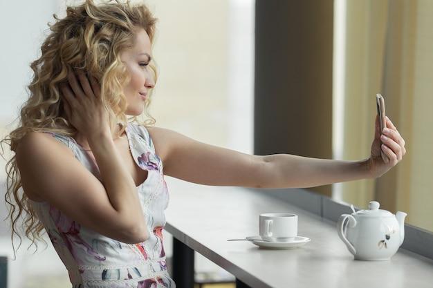 Jong blondemeisje die zelfportret op haar slimme telefoon maken.