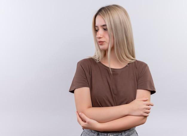 Jong blondemeisje die zich met gesloten houding bevinden die linkerkant op geïsoleerde witte muur met exemplaarruimte bekijken