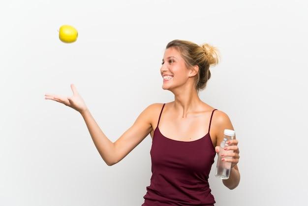 Jong blondemeisje met een appel en met een fles water