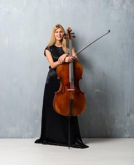 Jong blondemeisje met haar cello op geweven muurachtergrond