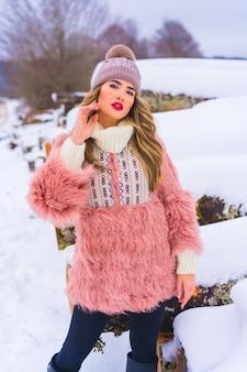Jong blondemeisje met roze bontjasje en purpere hoed in de sneeuw. naast enkele bomen die met ijs zijn gekapt, winterlevensstijl