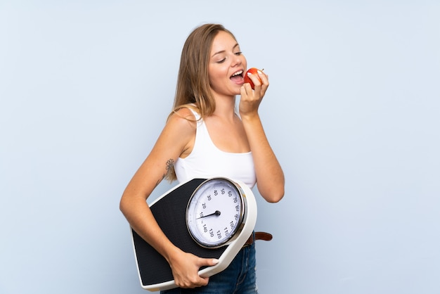 Jong blondemeisje met weegmachine en met een appel over geïsoleerde blauwe witte muur