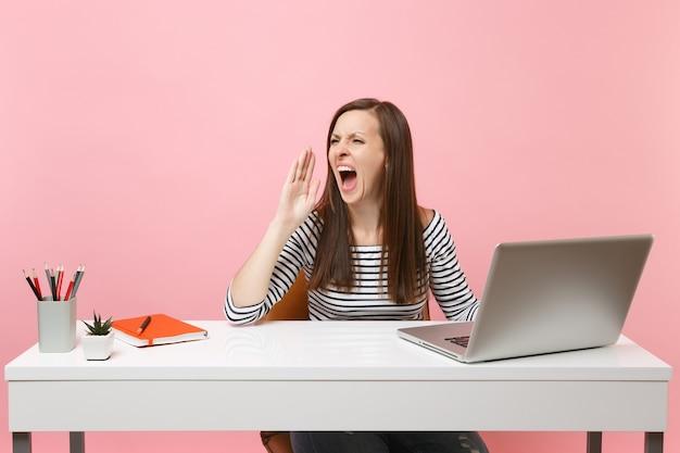 Jong boos meisje schreeuwen tijdens het werken aan project zittend op kantoor met hedendaagse pc-laptop geïsoleerd op pastel roze achtergrond. prestatie zakelijke carrière concept. kopieer ruimte voor advertentie.