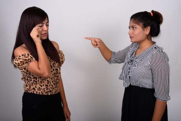 Jong boos tienermeisje wijzend op het jonge vrouw huilen