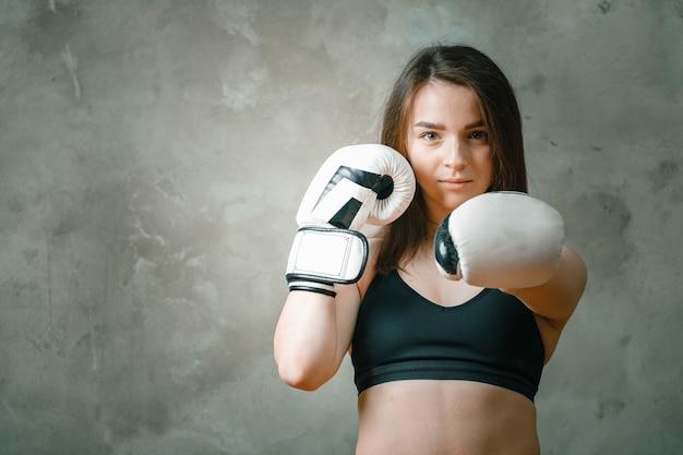 Jong boos vechtersmeisje met witte handschoenen die praktijk bestrijden