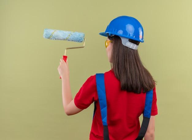 Jong bouwersmeisje met blauwe veiligheidshelm en met veiligheidsbril staat met rug naar camera en houdt verfroller op geïsoleerde groene achtergrond