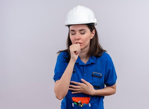 Jong bouwersmeisje met witte veiligheidshelm en blauw uniform beweert te hoesten op geïsoleerde witte achtergrond met exemplaarruimte