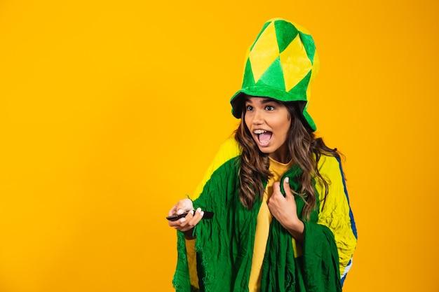Jong braziliaans fanmeisje met controller in de hand klaar om naar het braziliaanse spel te kijken