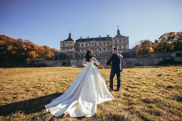 Jong bruidspaar gaat hand in hand rechtdoor, op de achtergrond van een middeleeuws kasteel, herfstdag
