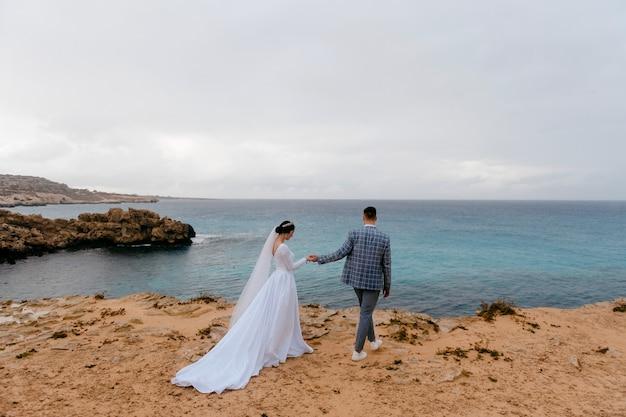 Jong bruidspaar wandelen op een rotsachtig strand in de buurt van de blauwe zee