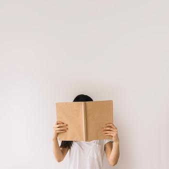 Jong brunette verbergend gezicht achter boek