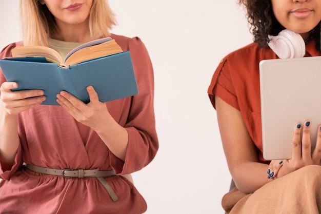 Jong casual blond vrouwelijk leesboek terwijl haar vriend van een gemengd ras met digitale tablet dichtbij zit en naar audioboek luistert