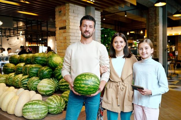 Jong casual gezin van drie die rijpe watermeloen kopen terwijl ze in grote supermarkt staan bij fruitvertoning