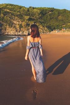 Jong caucassian meisje met een blauwe jurk possing op zarautz strand, baskenland.