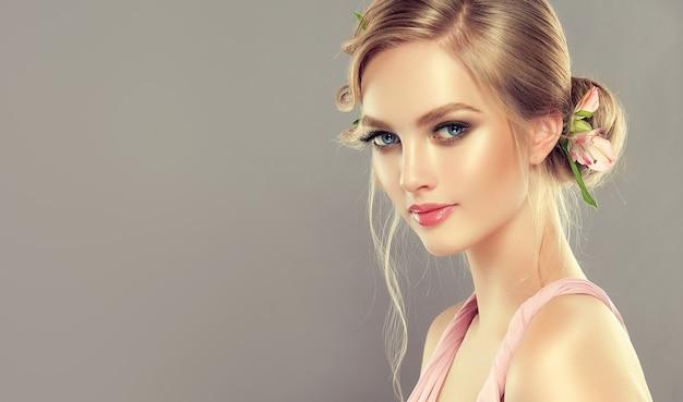 Jong, charmant, blauwogig model met blond haar verzameld in elegant kapsel met verse bloemen. kapperskunst, haarkleuring, mkeup en cosmetica.