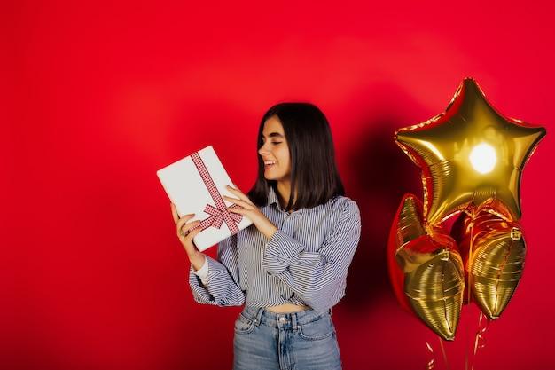 Jong charmant meisje houdt witte huidige doos met rode giftboog en dichtbij is drie gouden ballons.