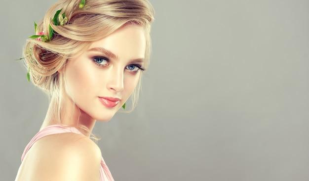 Jong, charmant model met blauwe ogen en blond haar verzameld in een elegant kapsel met verse bloemen. kapperskunst, haarkleuring en schoonheidsproducten.