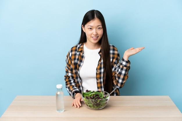 Jong chinees meisje dat een denkbeeldige copyspace van de saladeholding op de palm eet om een advertentie op te nemen