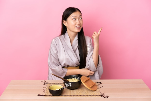 Jong chinees meisje dat kimono draagt en noedels eet die een geweldig idee benadrukken