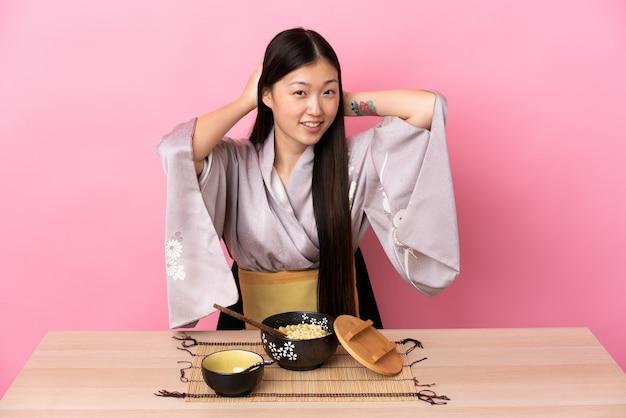 Jong chinees meisje dat kimono draagt en noedels eet het lachen