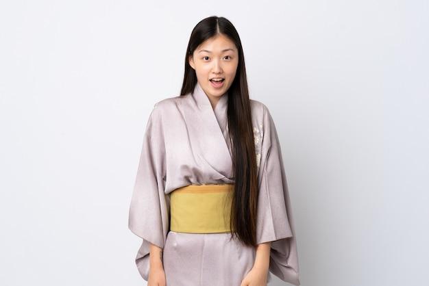 Jong chinees meisje dat kimono met verrassingsgelaatsuitdrukking draagt