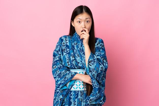 Jong chinees meisje dat kimono over geïsoleerde achtergrond draagt die verrast en geschokt terwijl naar rechts kijkt