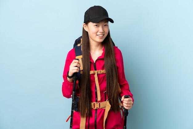 Jong chinees meisje dat met rugzak en trekkingspolen over blauwe muur omhoog terwijl het glimlachen kijkt