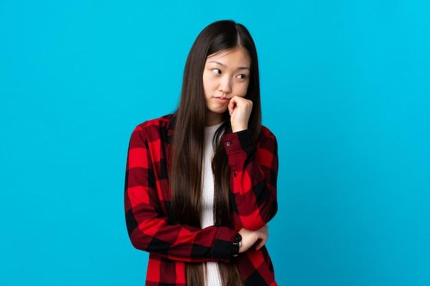 Jong chinees meisje dat met vermoeide en verveelde uitdrukking wordt geïsoleerd
