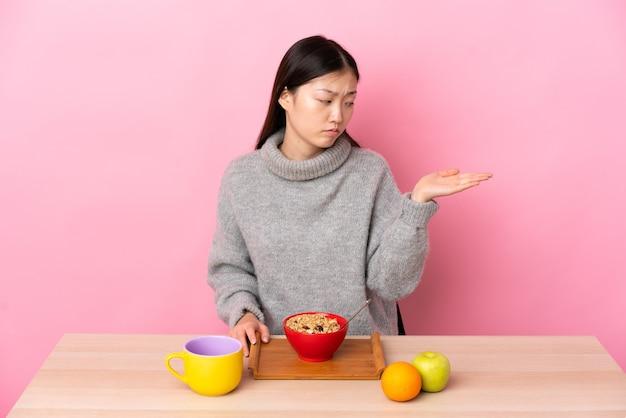 Jong chinees meisje dat ontbijt in een copyspace van de lijstholding met twijfels houdt