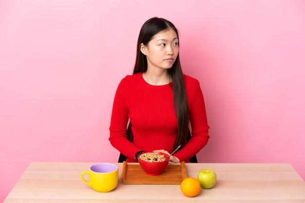 Jong chinees meisje dat ontbijt in een lijst heeft die naar de kant kijkt
