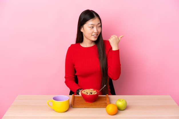 Jong chinees meisje dat ontbijt in een lijst heeft die naar de kant wijst om een product te presenteren