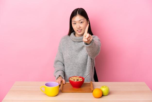 Jong chinees meisje dat ontbijt in een lijst heeft en een vinger opheft