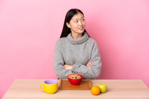 Jong chinees meisje dat ontbijt in een lijst heeft terwijl het glimlachen omhoog kijkt