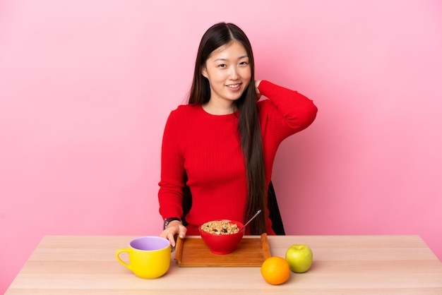 Jong chinees meisje dat ontbijt in een lijst het lachen