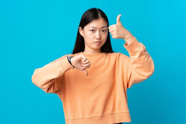 Jong chinees meisje dat op geïsoleerd blauw goed-slecht teken maakt. onbeslist tussen ja of niet