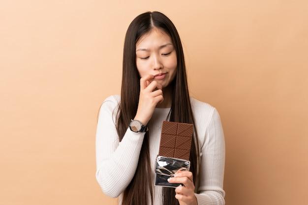 Jong chinees meisje die een chocoladetablet nemen en twijfels hebben